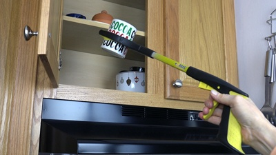 Reacher Grabber retrieving mug from cupboard