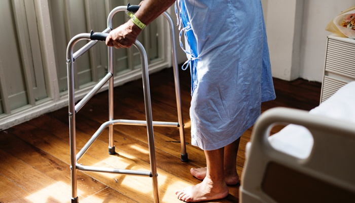 Older adult using walker wearing Fall Risk wristband
