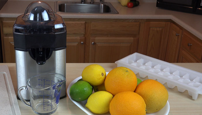 Cuisinart Citrus Juicer with Pulp Control next to assortment of citrus fruits lemons, limes, and oranges
