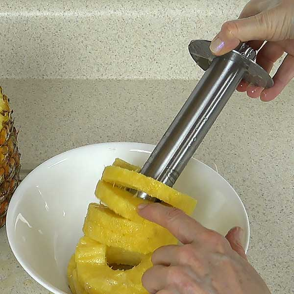 Turning corer upside down and sliding off pineapple rings