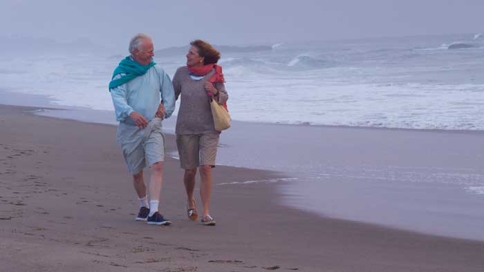 How to Prepare for Old Age? Older Couple Walking Along the Beach