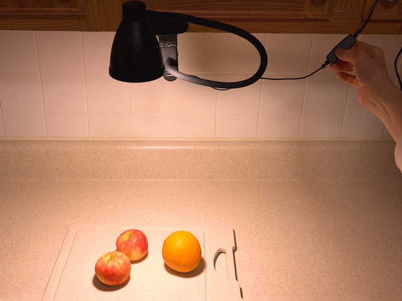 The gooseneck desk lamp clamped to a kitchen cabinet to light the counter top